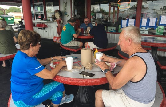 Customers at Burger Inn in Melbourne try not to let the pesky lovebugs bother them during lunch Tuesday.