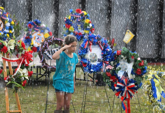 An act of respect. When a brief but heavy rain began, 8- year-old Ajalynn Fields  continued to salute for several minutes in front of the wreath for the Veterans Transitional Facility. Monday's presentation of wreaths and opening ceremony at the Vietnam Traveling Memorial Wall, which will be set up until May 12. It is part of The 32nd Annual Vietnam and All Veterans Reunion, a free event open to the public at Wickham Park in Melbourne May 9-12.
