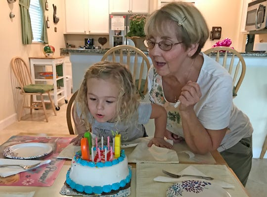 Isabella blows out candles with the help of her grandmother to celebrate her birthday last year.