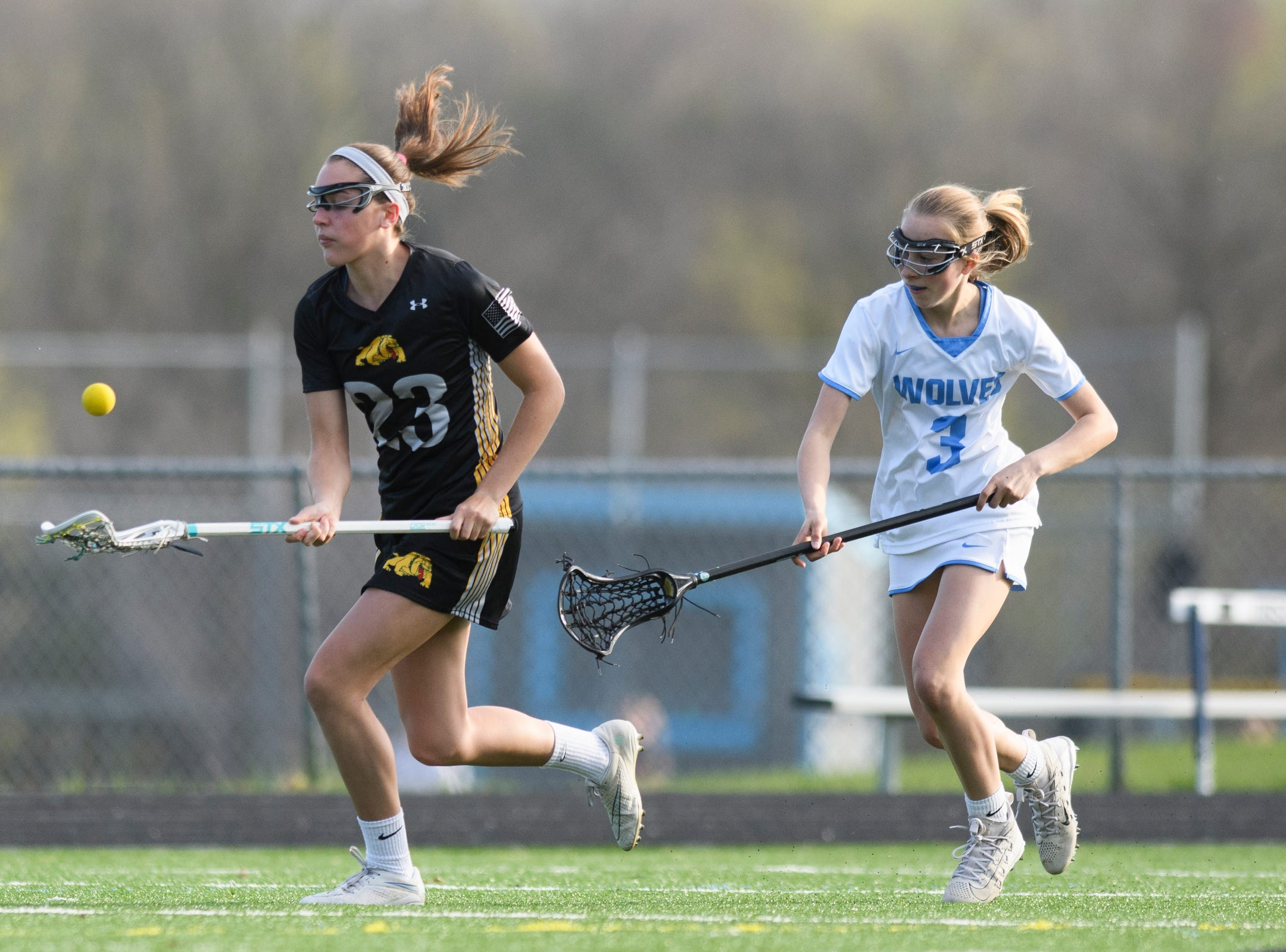 Burr and Burton's Sydney Goldfarb (23) plays the ball; as she runs down the field past South Burlington's Lindsey Booth (3) during the high school girls lacrosse game between Burr and Burton Bulldogs and the South Burlington Wolves at Munson Field on Monday afternoon May 6, 2019 in South Burlington, Vermont.