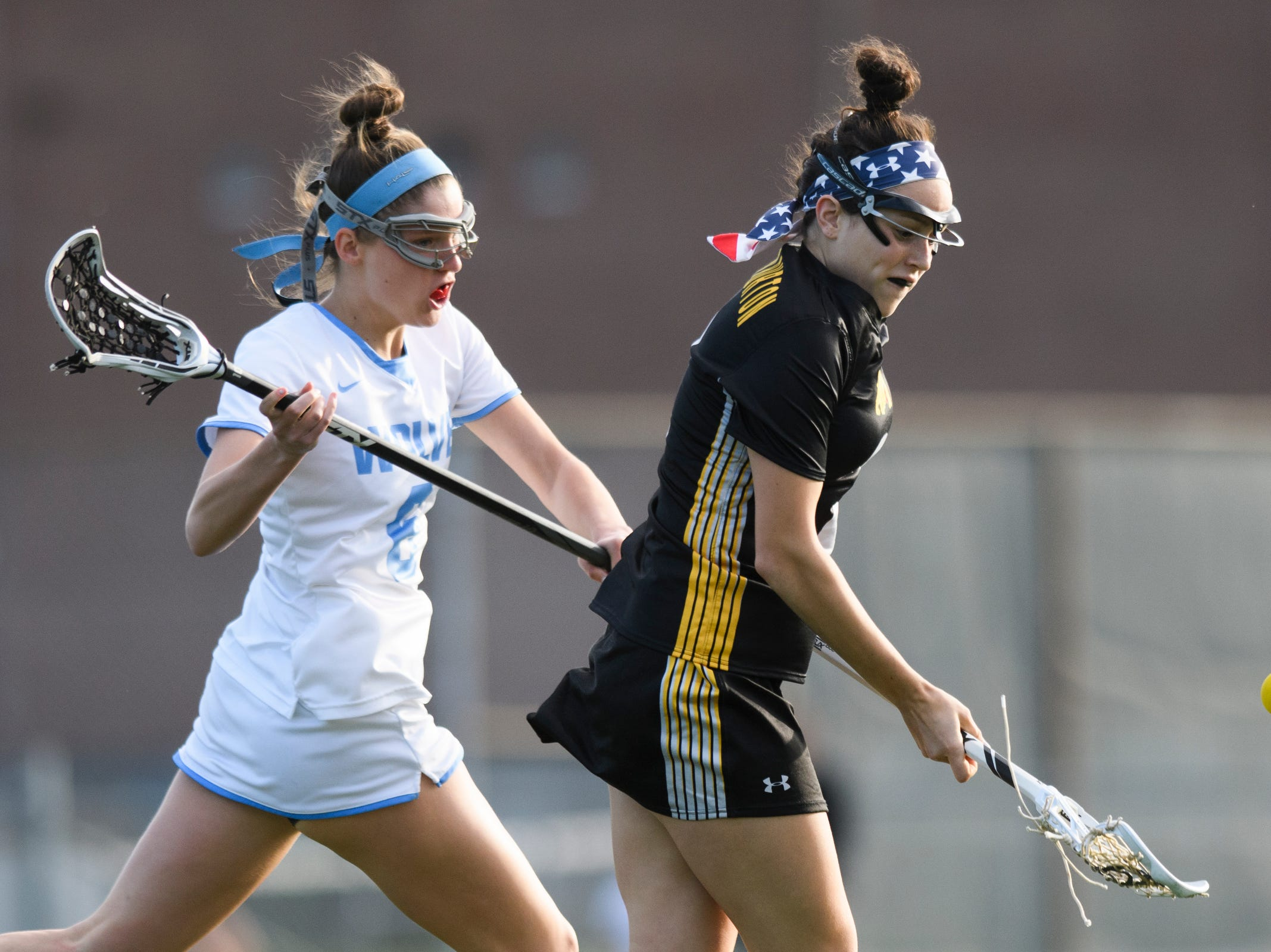 Burr and Burton's Fiona McMahon (2) plays the ball as she runs past South Burlington's Kathryn DeMag (6) during the high school girls lacrosse game between Burr and Burton Bulldogs and the South Burlington Wolves at Munson Field on Monday afternoon May 6, 2019 in South Burlington, Vermont.
