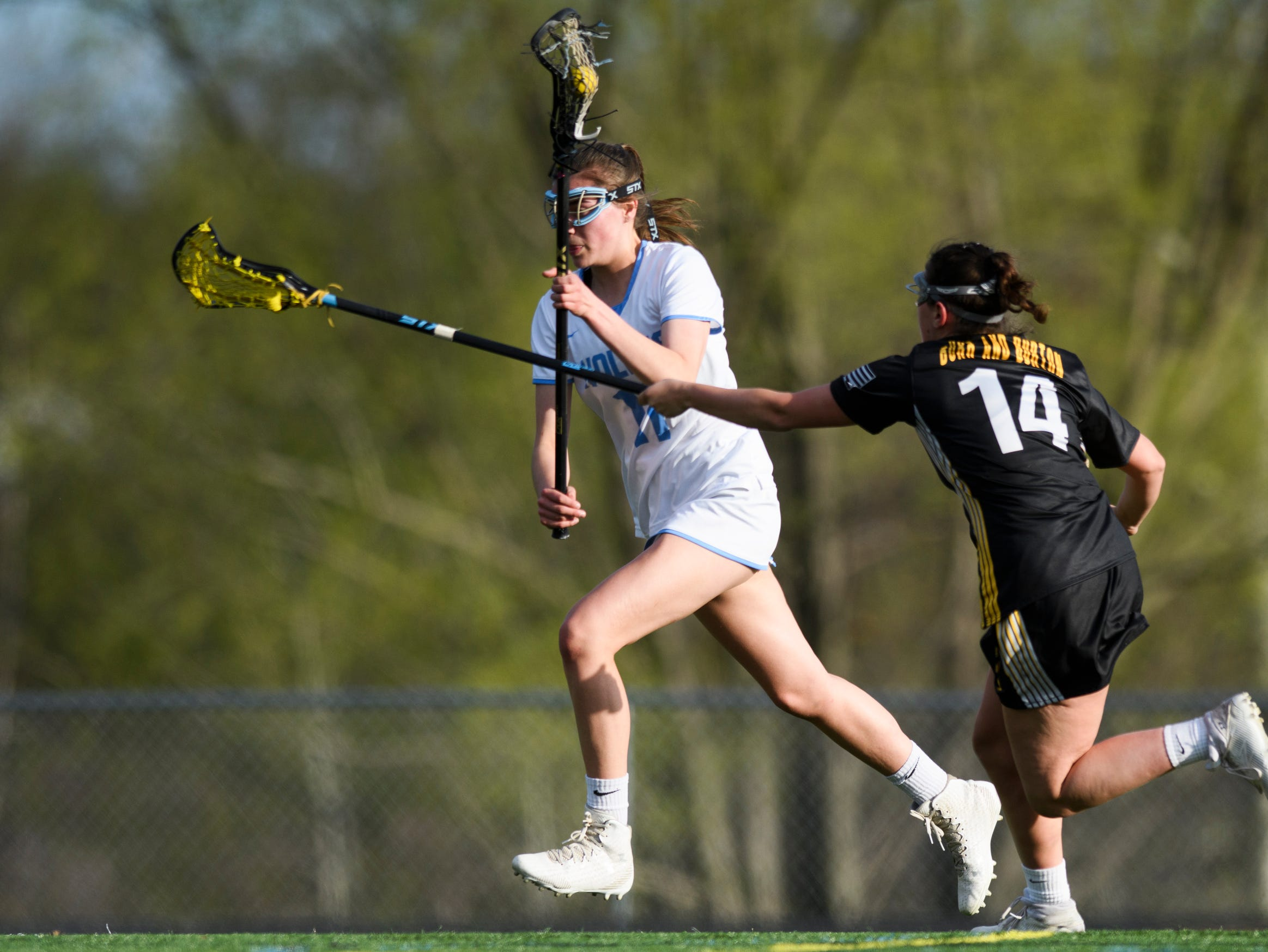 South Burlington's Christina March (11) runs down the field past Burr and Burton's Charleigh Carthy (14) during the high school girls lacrosse game between Burr and Burton Bulldogs and the South Burlington Wolves at Munson Field on Monday afternoon May 6, 2019 in South Burlington, Vermont.