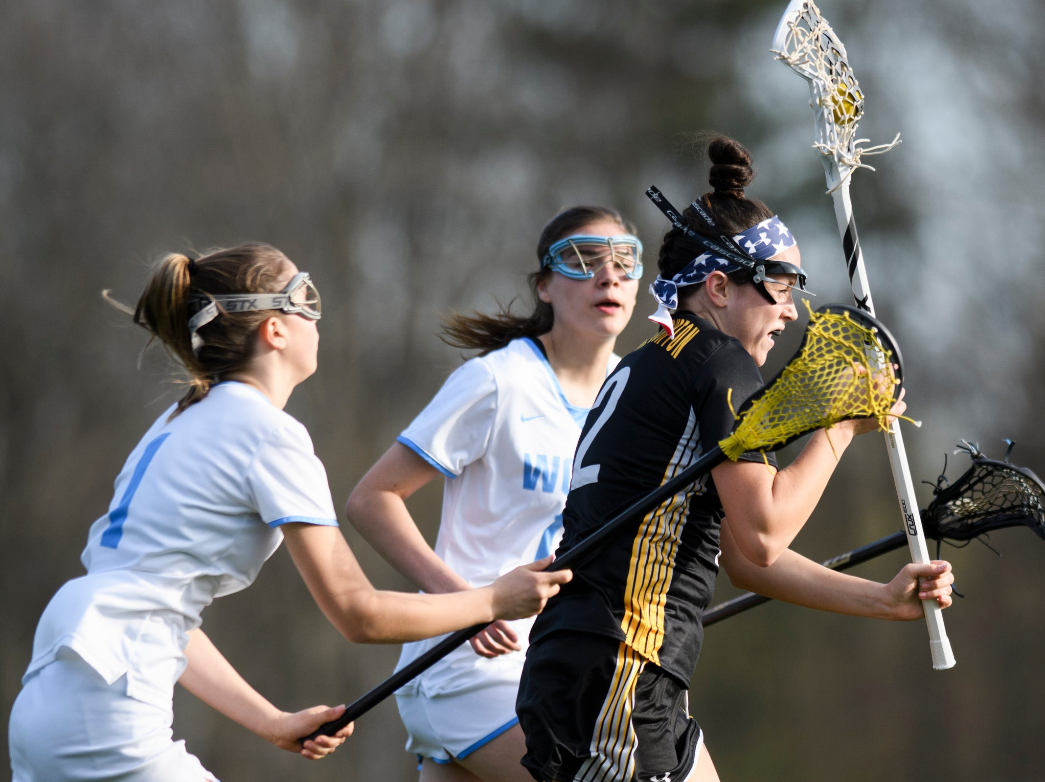 Burr and Burton's Fiona McMahon (2) runs between South Burlington's Sam Crane (1) and Christina March (11) during the high school girls lacrosse game between Burr and Burton Bulldogs and the South Burlington Wolves at Munson Field on Monday afternoon May 6, 2019 in South Burlington, Vermont.