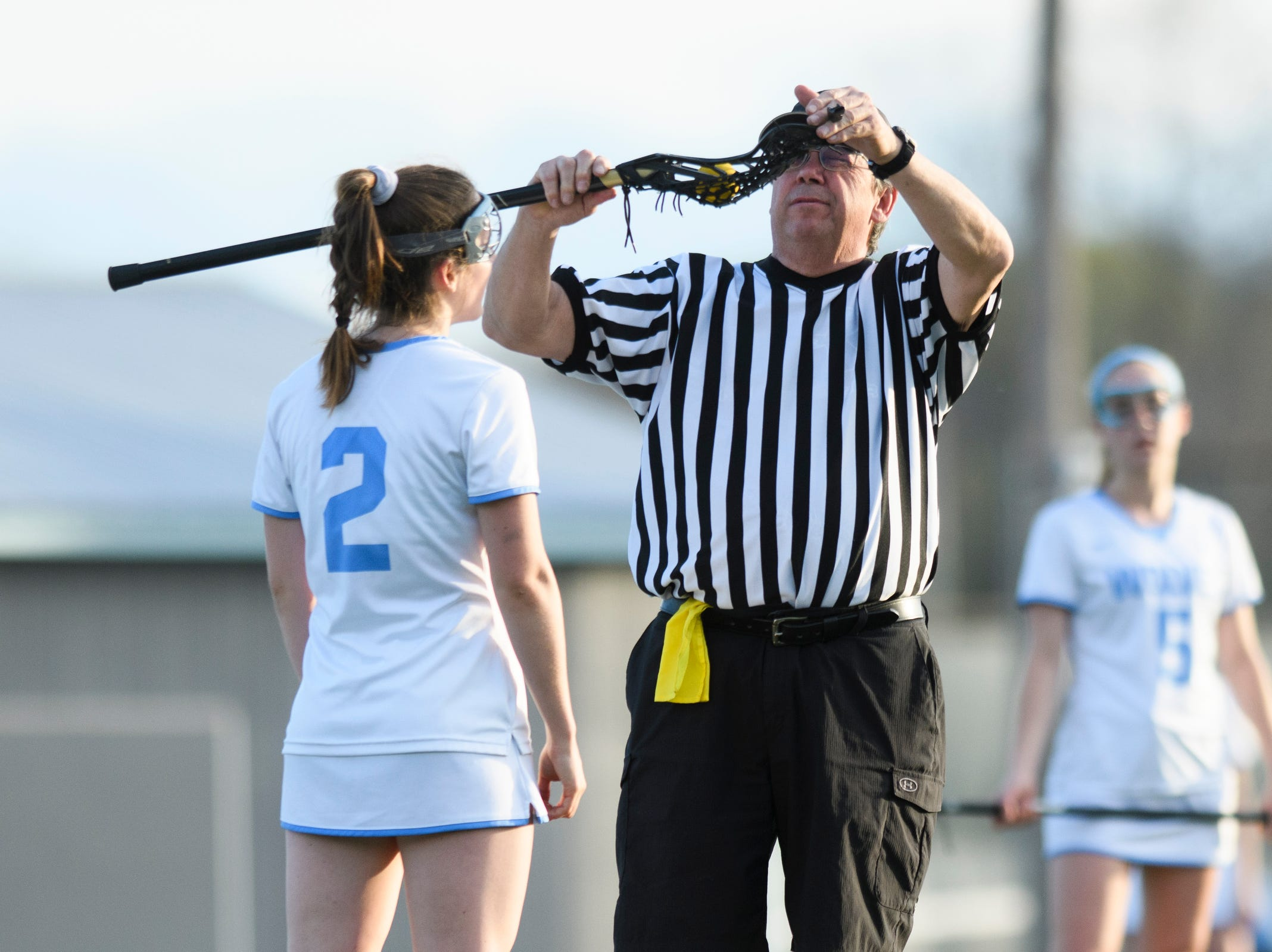 Referee Kevin Hebert checks the stick of South Burlington's Kate Hall (2) during the high school girls lacrosse game between Burr and Burton Bulldogs and the South Burlington Wolves at Munson Field on Monday afternoon May 6, 2019 in South Burlington, Vermont.