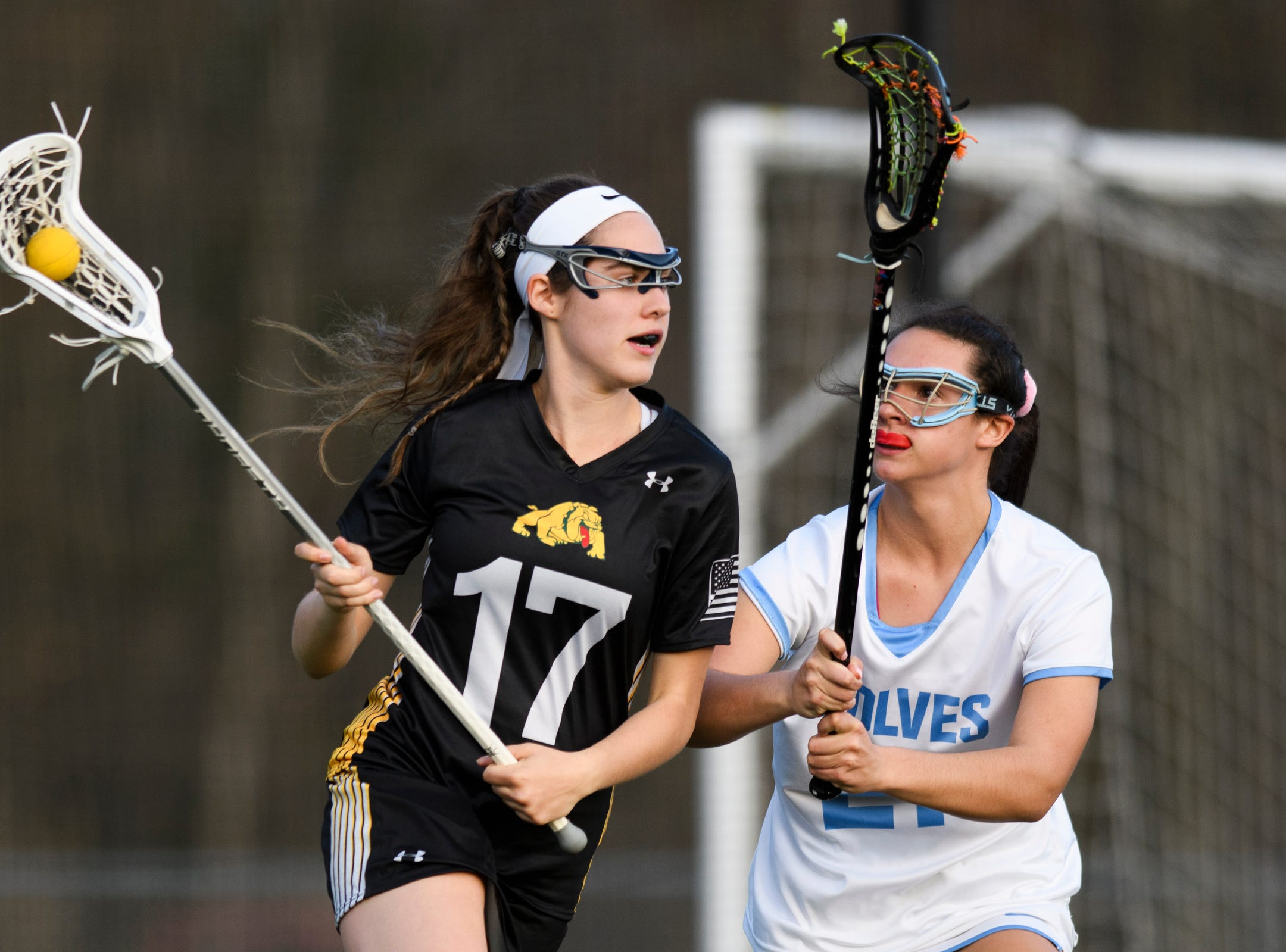 Burr and Burton's Ava Marshall (17) runs past South Burlington's Danielle Sleiman (21) with the ball during the high school girls lacrosse game between Burr and Burton Bulldogs and the South Burlington Wolves at Munson Field on Monday afternoon May 6, 2019 in South Burlington, Vermont.