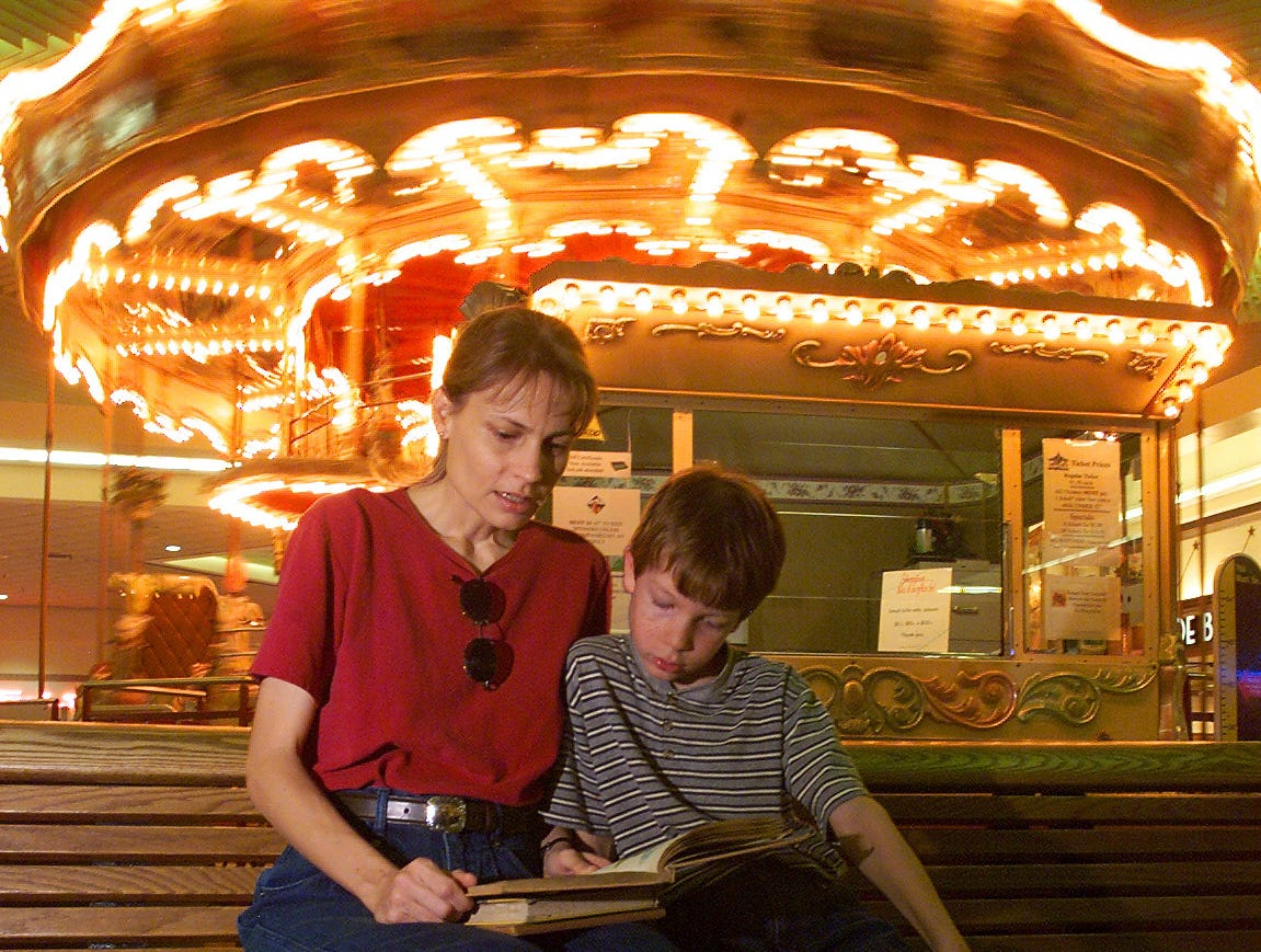 """Heidi Bond reads """"Dan Frontier with the Indians"""" with her son Steven, 8, next to the carousel at the Out-of-Print book sale and Silent Auction raising money for the Janet F. Harte Public Library at Padre Staples Mall in March 2000."""