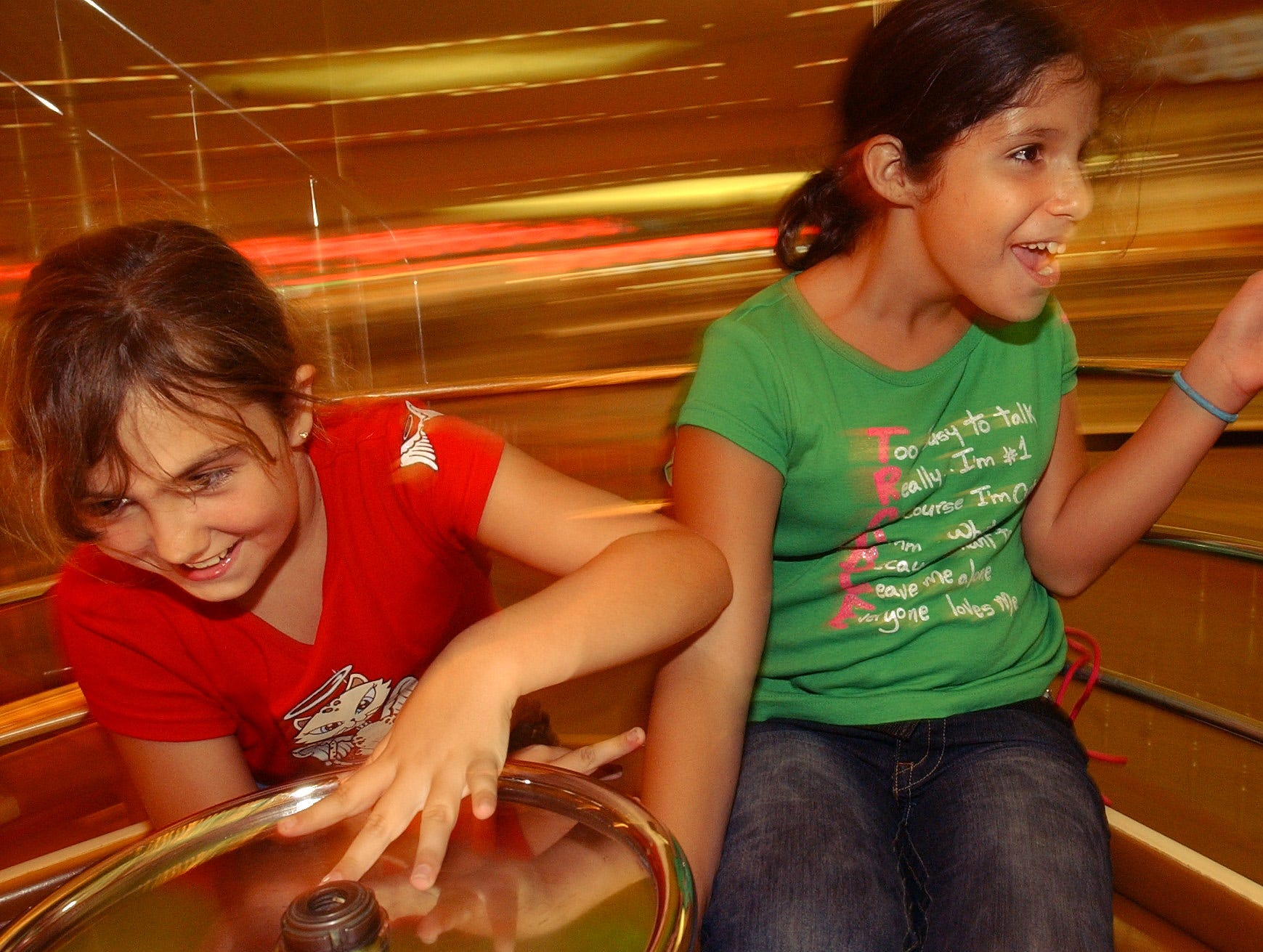 Vegas and Sierra Longlois ride the carousel in Padre Staples Mall in Corpus Christi on July 21, 2004.