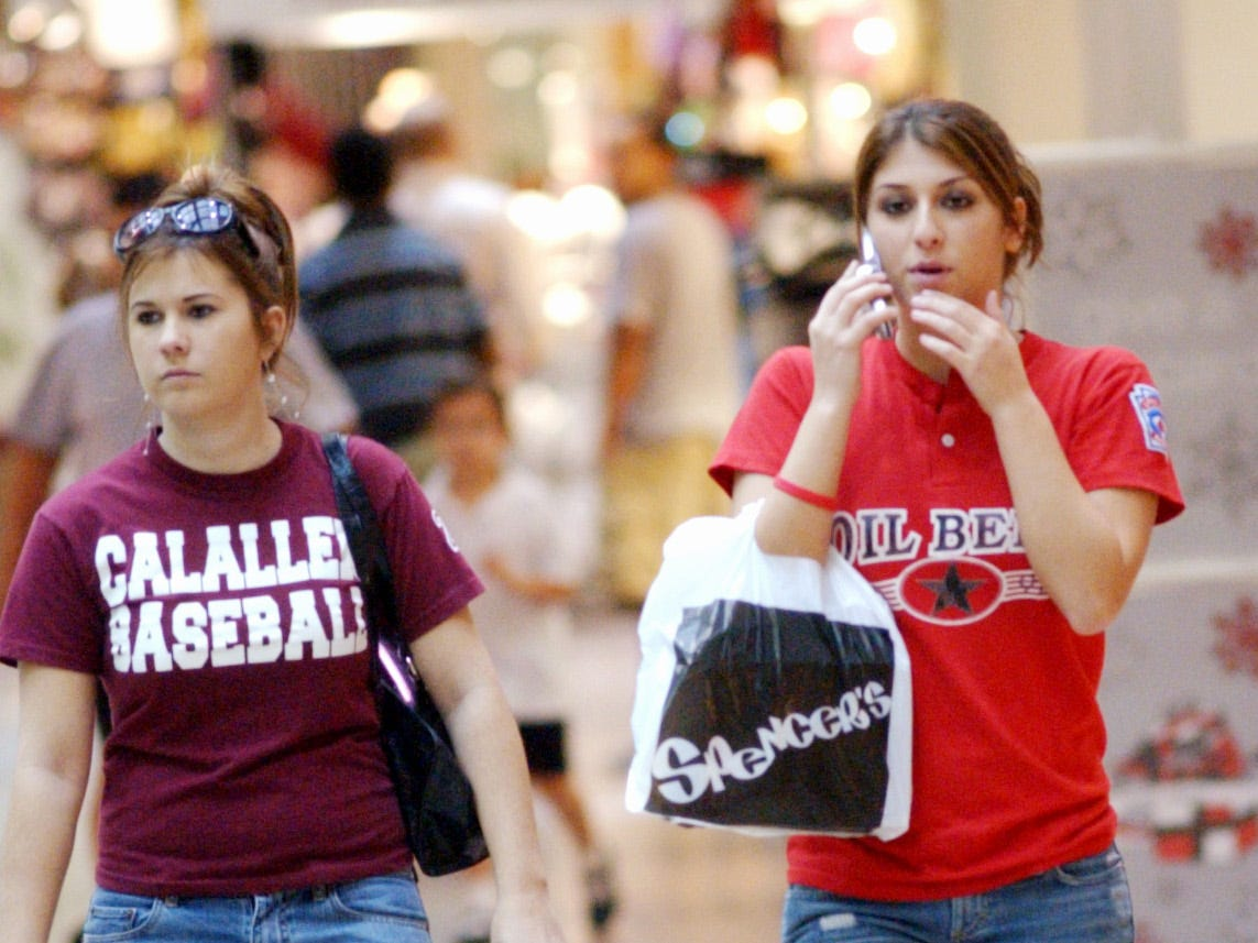 Tiffany Callihan, left, and Kandice Garcia, right carry their bags from Wet Seal and Spencer's while shopping at Padre Staples Mall on DEc. 18, 2005.