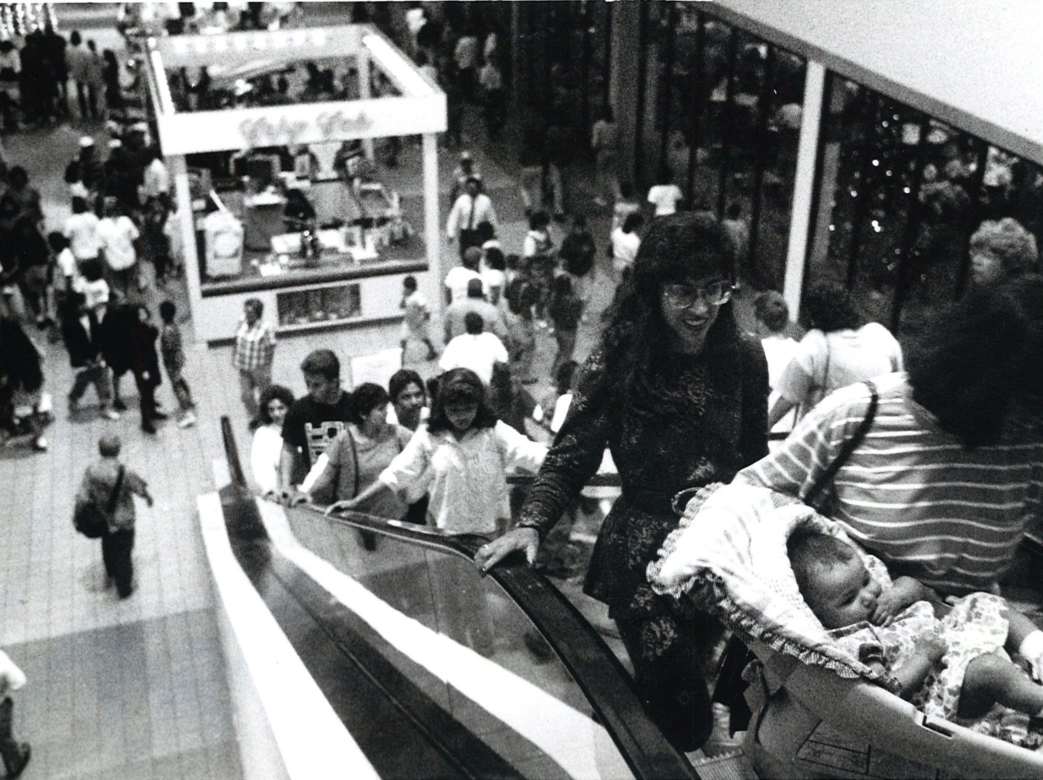Patrons of Padre Staples Mall crowd the escalators during the first official day of the Christmas shopping season in 1990.