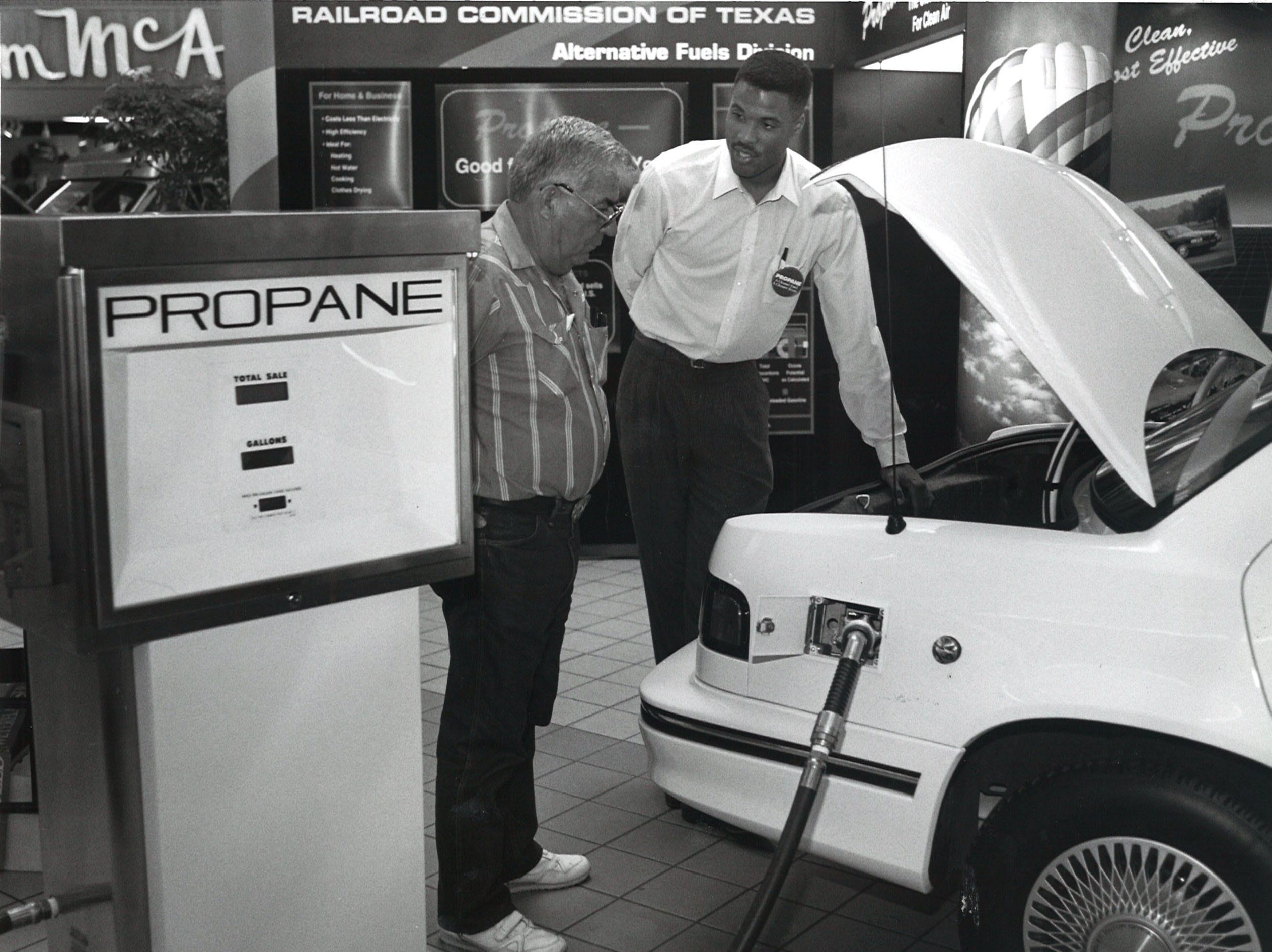 Elizardo Gutierrez (left), looks at a display vehicle in the center court of Padre Staples Mall in Corpus Christi as Clayton Whitaker of the Texas Railroad Commission explains the propane gas pump on Sept. 23, 1993.