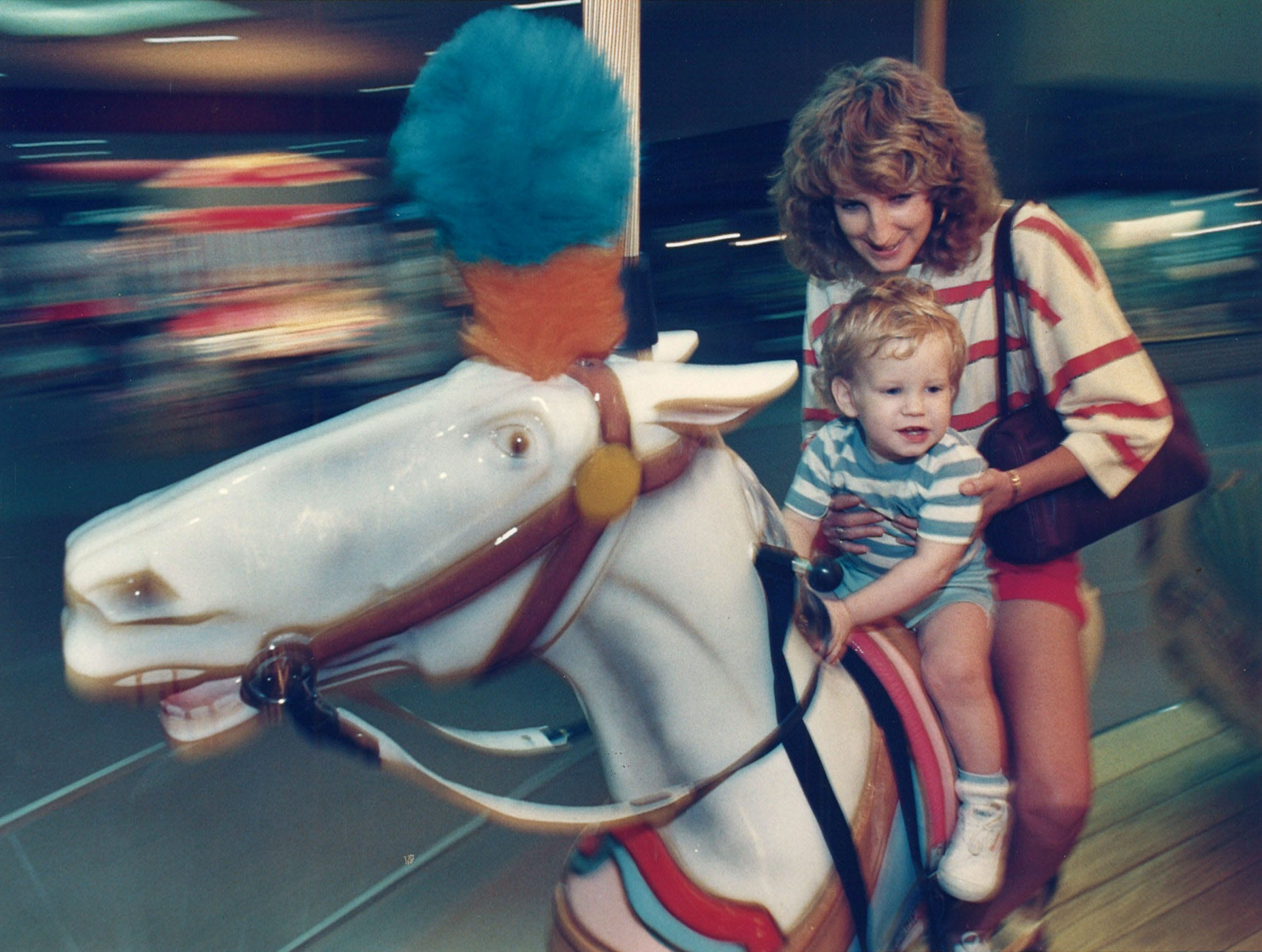 Mona Hatridge and 18-month-old son Reese spin around the carousel in Padres Staples mall on Oct. 26, 1988.