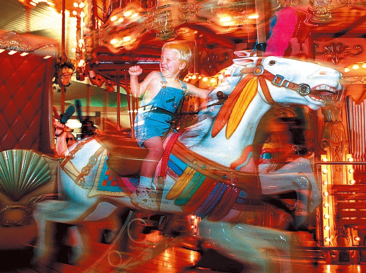 D.J. Favor, 3, waves at his mother, Abbey, as he passes by on the carousel at the Padre Staples Mall. D.J. was at the mall shopping with his mother and his aunt on July 17, 1997.
