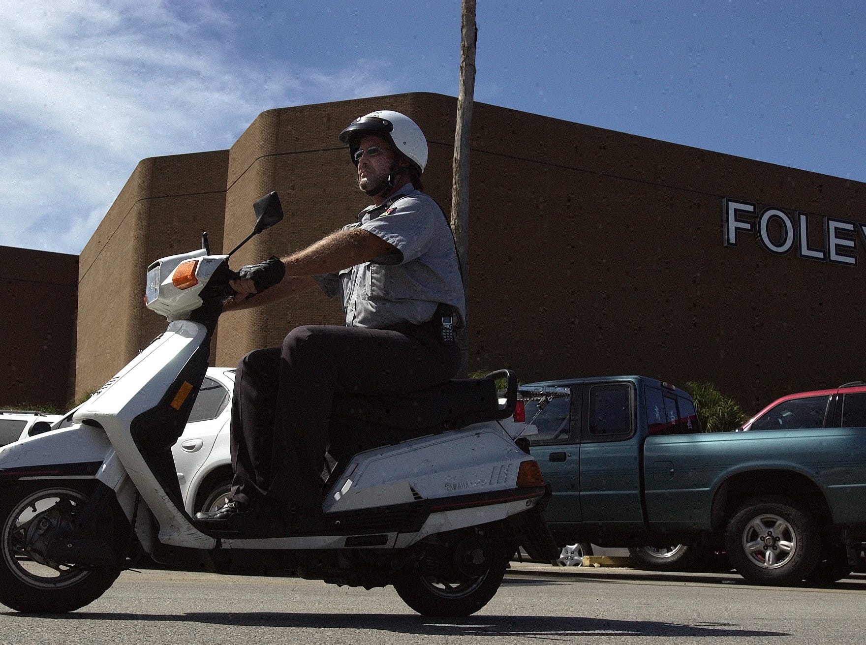 Padre Staples Mall security guard Ron Beem patrols the parking lot atop a moped on Aug. 25, 2003.  The mall uses a team of 13 people to monitor activity both inside and outside the building.