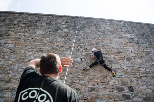 Climber Alexander Rosenberg demonstrates what it's like to scale a prison wall, as part of an art installation at Eastern State Penitentiary in Philadelphia, Pa. Thursday, May 2, 2019.
