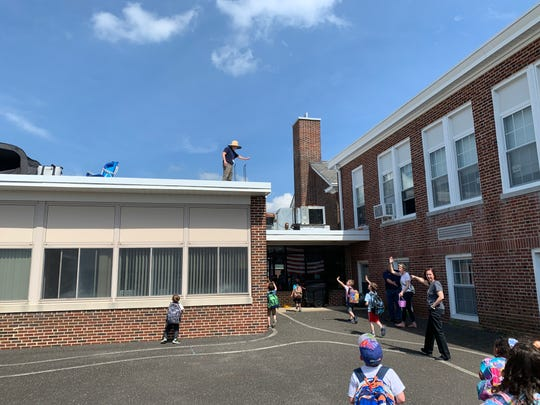 Aura School Principal Wayne Murschell makes good on his deal with his Elk Township students - if they read more than 200,000 minutes, he'll spend a night camping on the roof. He waved to students as they left school for the day May 7, 2019.
