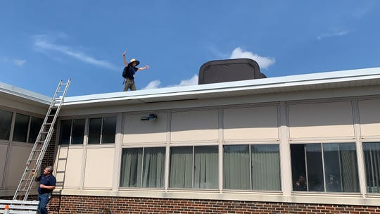 Aura School Principal Wayne Murschell makes good on his deal with his Elk Township students - if they read more than 200,000 minutes, he'll spend a night camping on the roof. He climbed the ladder to the rooftop May 7, 2019.