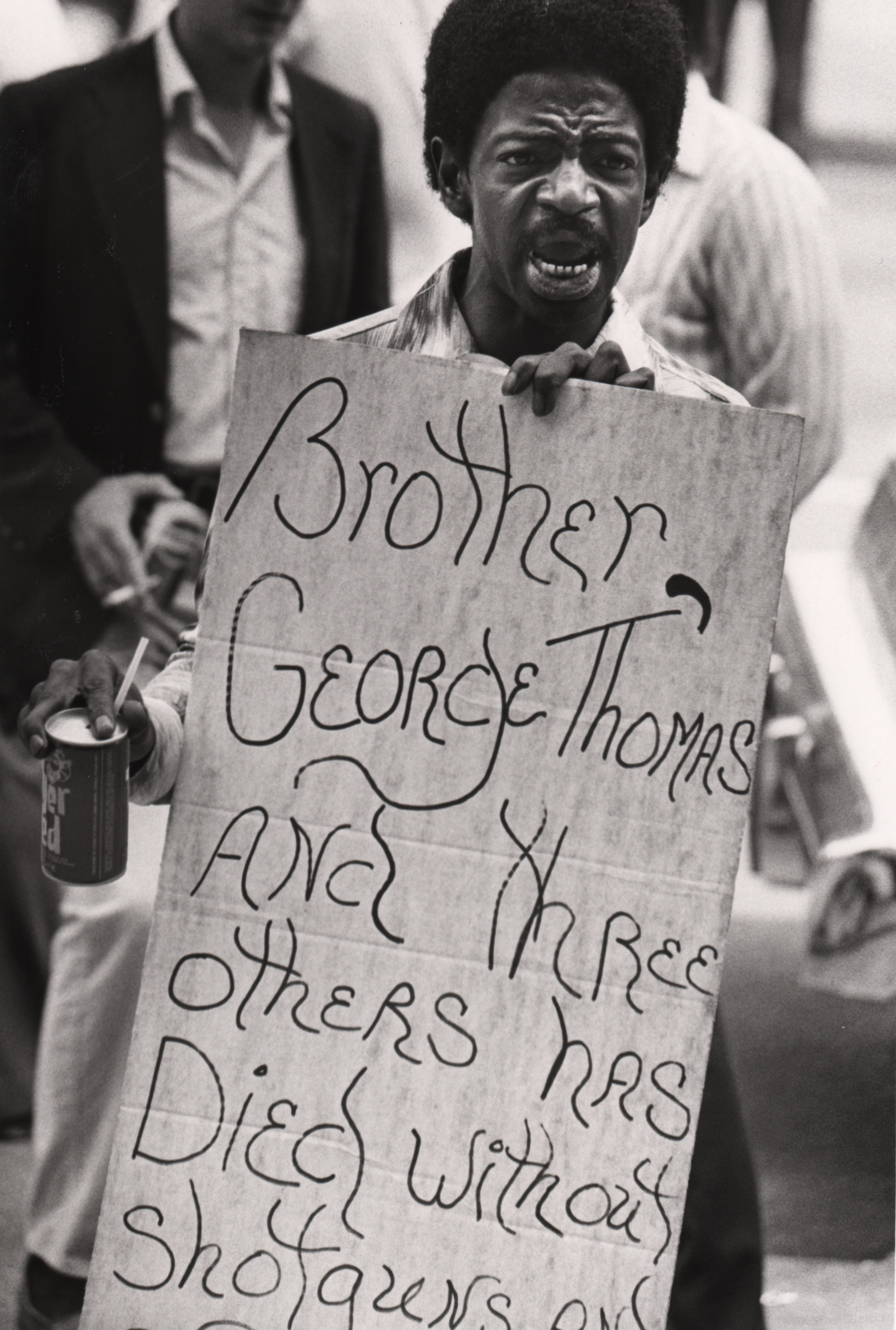"""A man holds a sign: """"Brother George Thomas and three others has died without shotguns..."""" as police marched on City Hall to demand greater protections on May 9, 1979 after taking a one-day strike."""