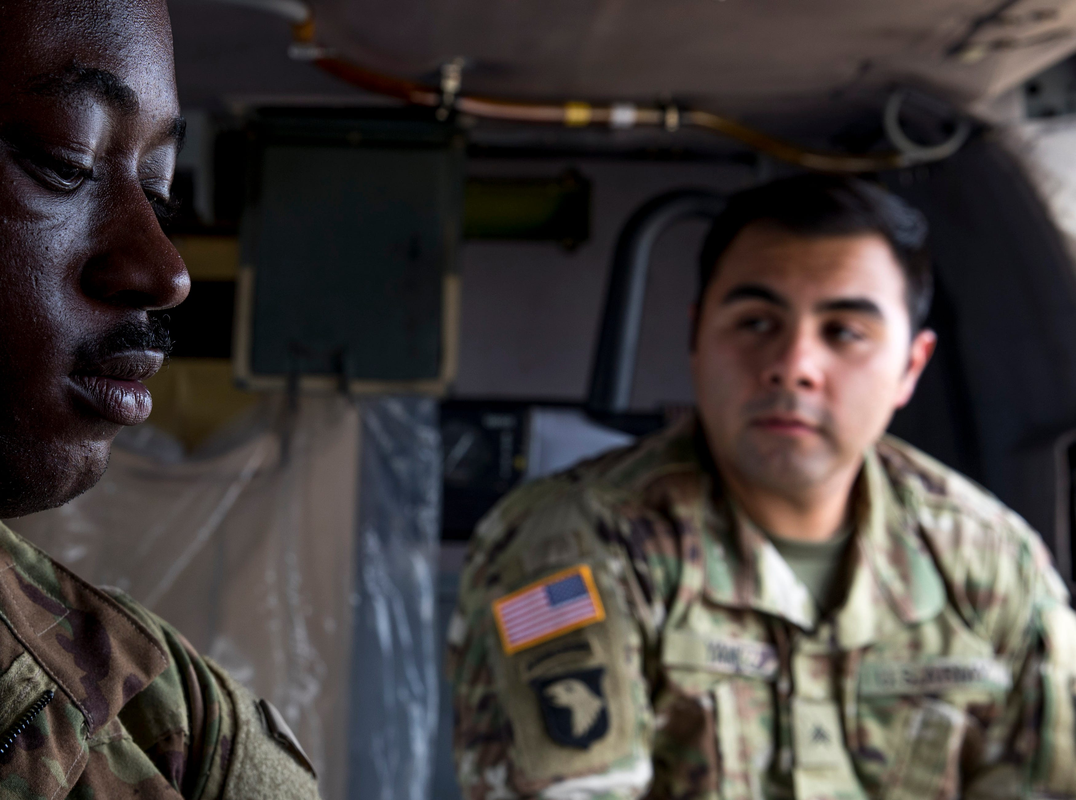 Sgt. Emmanuel Bynum, left, adjusts equipment inside a Black Hawk helicopter after sharing the story of his mission last year with Sgt. Armando Yanez.