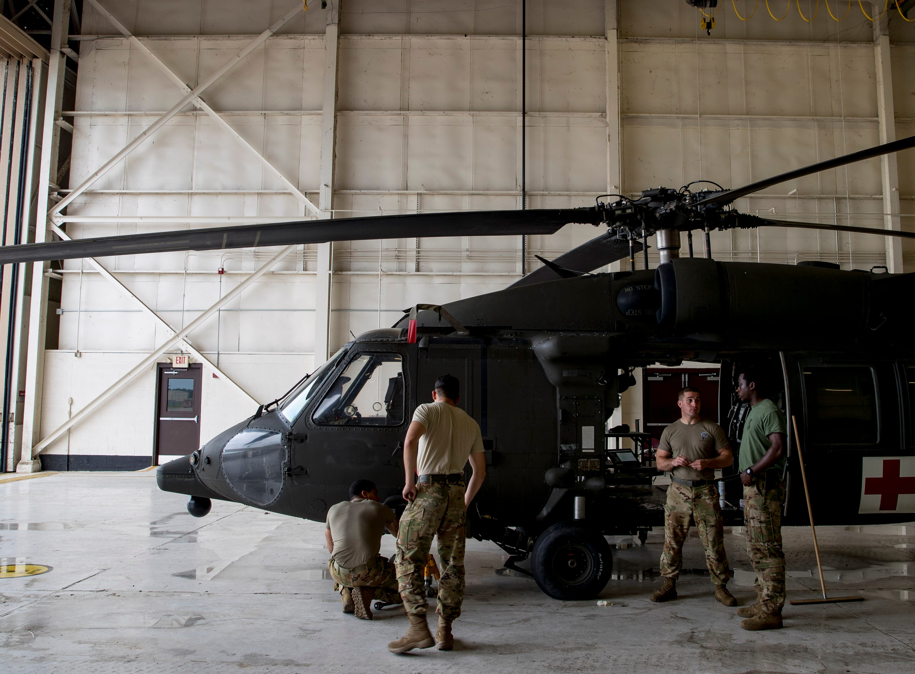 Sgt. Emmanuel Bynum, right, speaks with other soldiers maintaining a Black Hawk helicopter at Campbell Army Airfield in Fort Campbell, KY., on Wednesday, May 1, 2019.