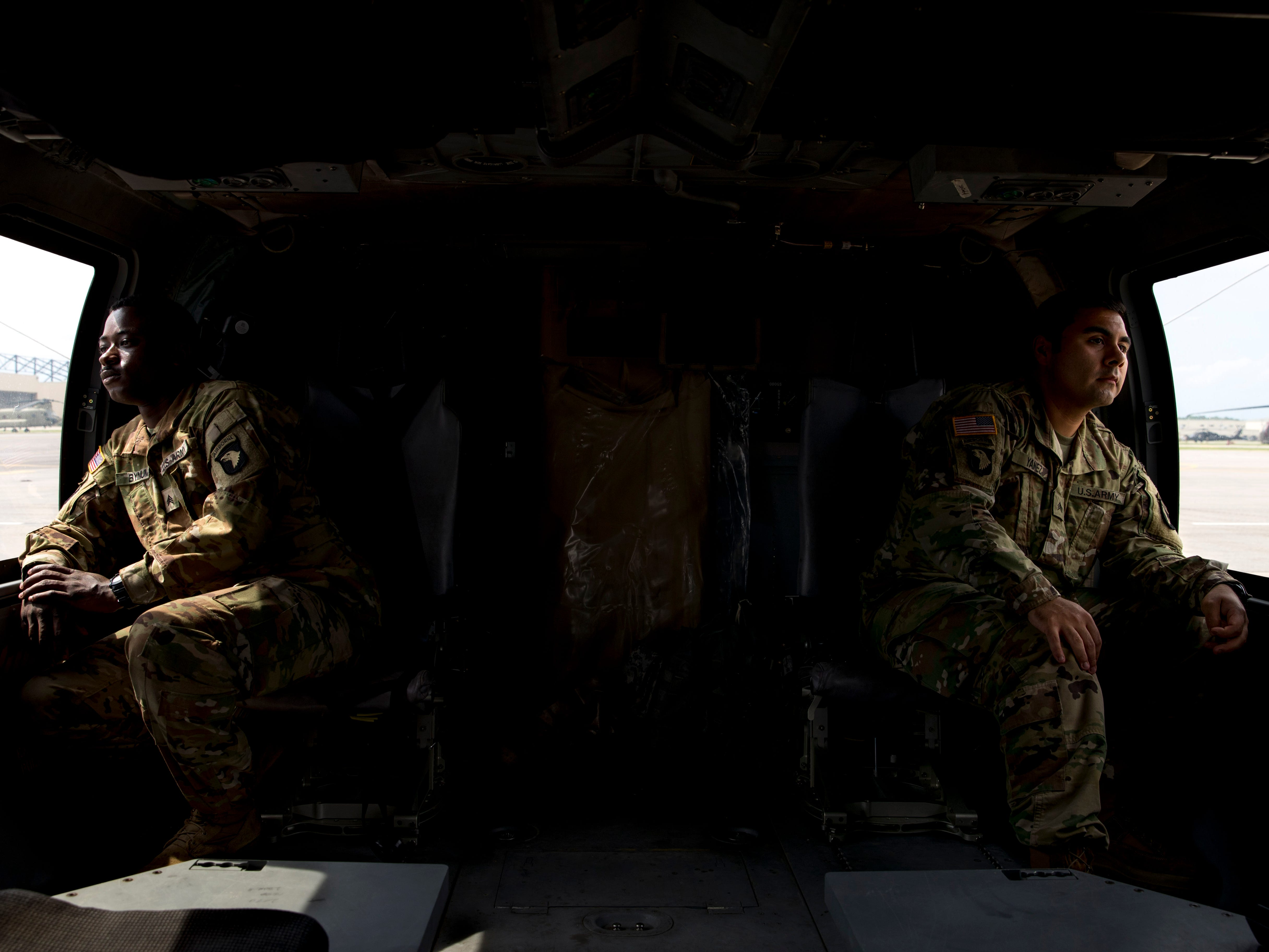 Sgt. Emmanuel Bynum, left, and Sgt. Armando Yanez peer out the windows of a Black Hawk helicopter Wednesday, May 1, 2019. The two were awarded Silver Stars for their actions during a mission in Afghanistan last year.