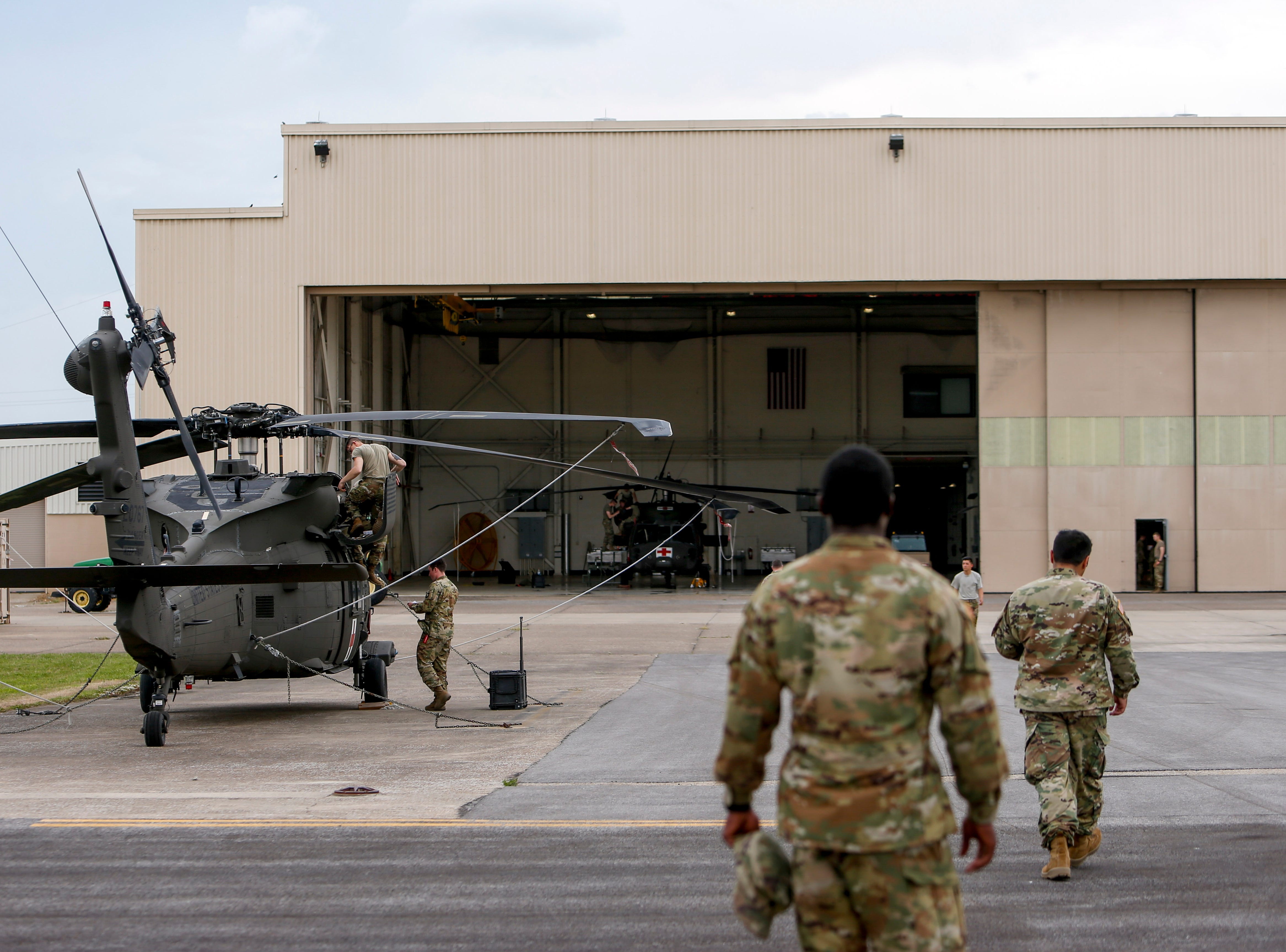 Sgt. Emmanuel Bynum, center, and Sgt. Armando Yanez, right, walk back to Hangar 3 at Campbell Army Airfield in Fort Campbell on Wednesday, May 1, 2019.