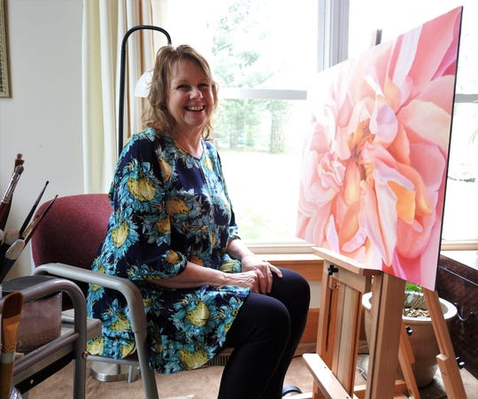 Melissa Maxwell of Warsaw works on a new oil painting of a flower in her home. She takes photos of flowers and uses them as references for her paintings.