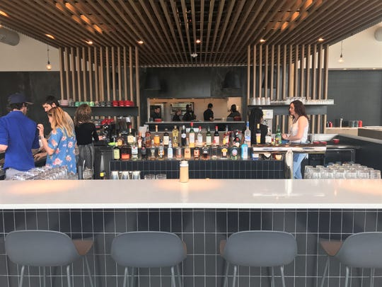 The bar is in the center of the restaurant with the open kitchen beyond at St. Kilda Surf & Turf.