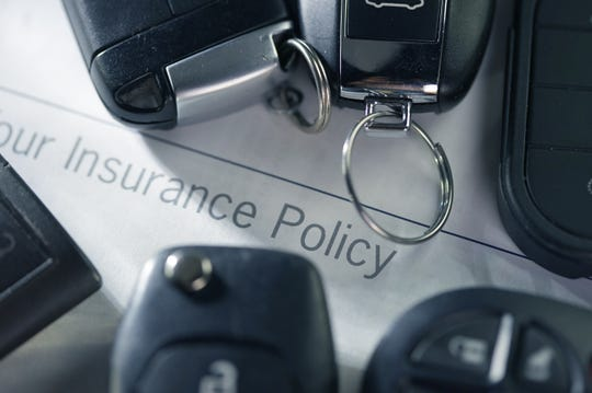 Shot of car key and insurance policy