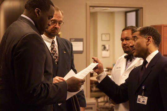Mayor-elect Kwame Kilpatrick gets last minute notes from former Justice Conrad Mallett, Jr., head of the Mayoral Transition Team, before announcing the teams to the media at Harper Hospital in 2001. Next to the mayor is Bob Berg, the mayor's spokesperson. To Justice Mallett's right is Dr. Arthur Porter, named as co-chair of the Health Department Restructuring, to create a plan to properly provide full health care for uninsured citizens in the City.