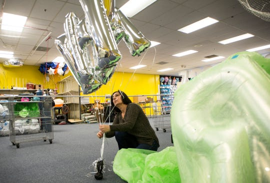 Nada Brikho, 56 of Shelby Two., ties off helium birthday balloons at Party Paradise in Sterling Heights, Mich., Tuesday, May 7, 2019.