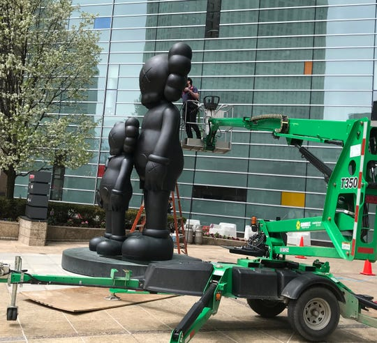 """Waiting"" sculpture by Kaws located in Detroit gets a cleaning on May 4, 2019, in preparation for the Kaws exhibit at the Museum of Contemporary Art Detroit."