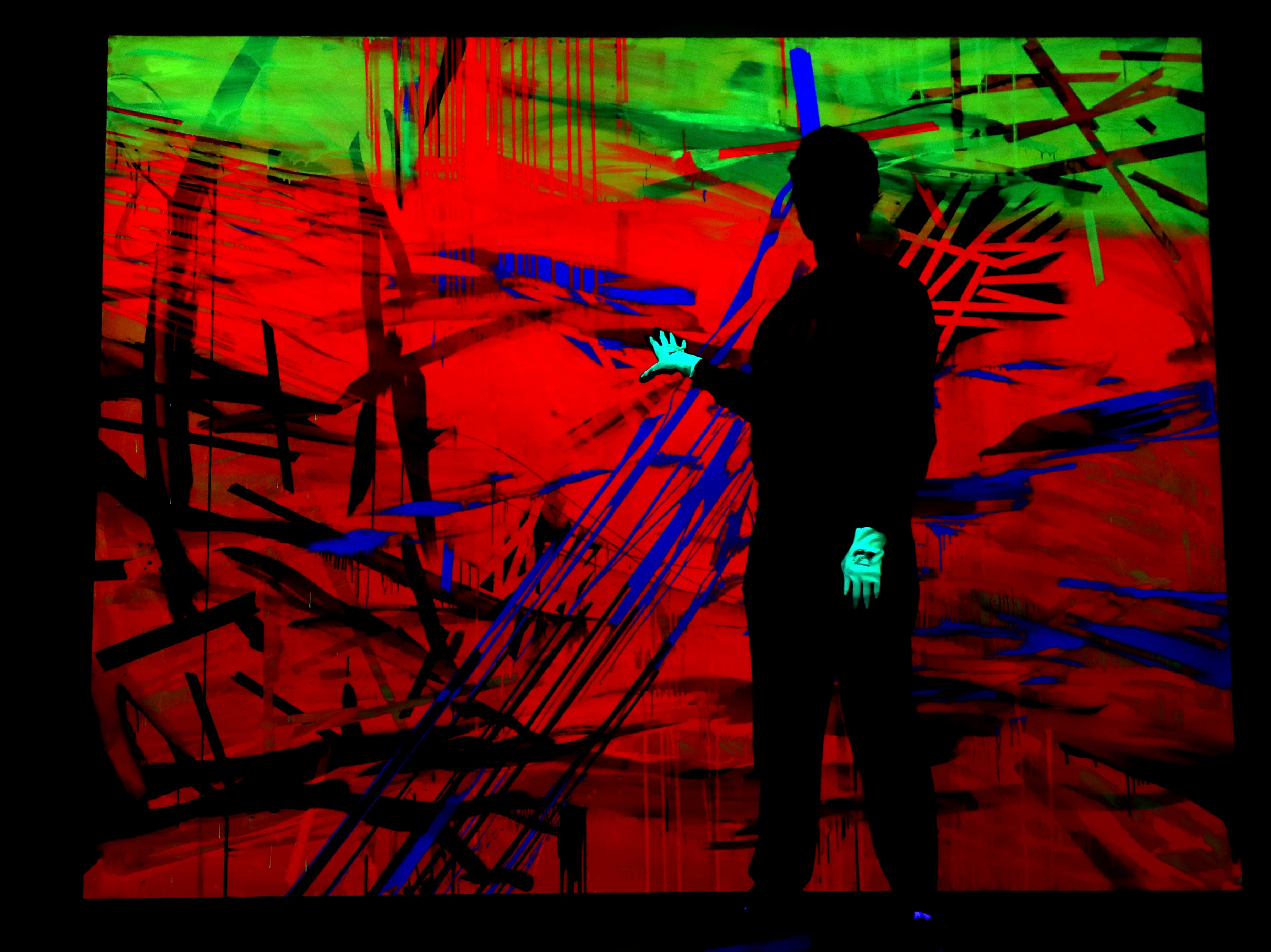 """Curator Patrizia Dander gestures at the works """"Black light paintings"""" by the US artist Jacqueline Humphries during a media- preview of the anniversary exhibition 'Forever Young - 10 Years Museum Brandhorst' in Munich, Germany, Tuesday, May 7, 2019. The exhibition will open on May 23 and, in addition to well-known and popular highlights from the collection, will also show numerous acquisitions that have been included in the Brandhorst Collection since 2009 and are now being presented for the first time in the museum. The exhibition comprises around 250 works by 45 artists, including Andy Warhol, Cy Twombly, Bruce Nauman, Cady Noland and Wolfgang Tilmans."""