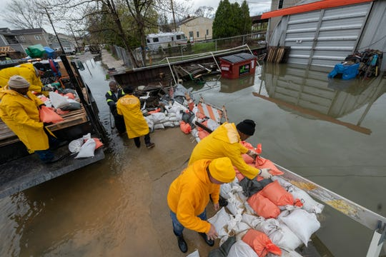 Detroit city employees and neighbors place sandbags around a residence on Klenk St. to stop canal flooding on Klenk Island in Detroit on  May 1.