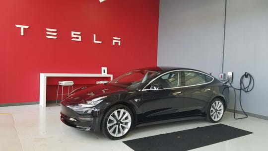 Customers meet their Tesla Model 3s for the first time in the delivery bay of the Tesla Cleveland dealer.