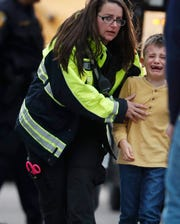 A young boy is led from a bus to a recreation center where students were reunited with their parents after a shooting at a suburban Denver middle school Tuesday, May 7, 2019, in Highlands Ranch, Colo.