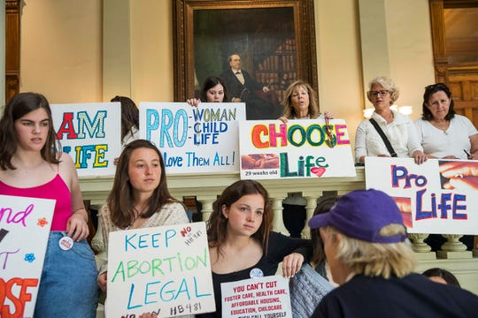 In this Friday, March 22, 2019, file photo, pro-abortion rights and anti-abortion demonstrators display their signs in the lobby of the Georgia State Capitol building.