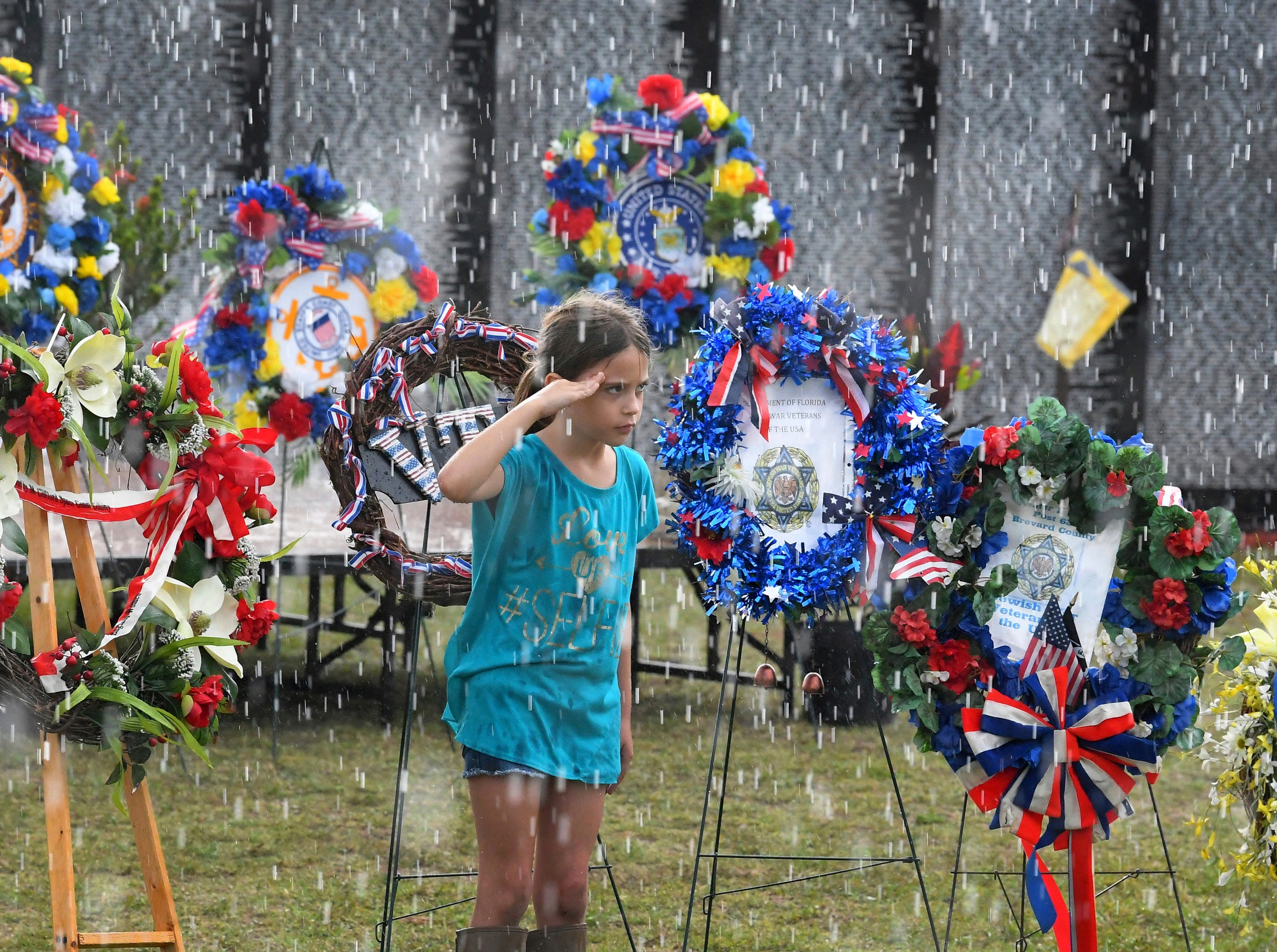 Eight-year-old Ajalynn Fields salutes in front of the wreath for the Veterans Transitional Facility, Monday, May 6, 2019, in Melbourne, Fla., during the presentation of wreaths and an opening ceremony at the Vietnam Traveling Memorial Wall, which will be up until May 12. It is part of the 32nd Annual Vietnam and All Veterans Reunion, a free event open to the public at Wickham Park in Melbourne May 9-12.