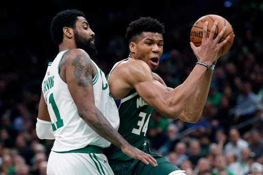 The Milwaukee Bucks' Giannis Antetokounmpo drives past Boston Celtics' Kyrie Irving.