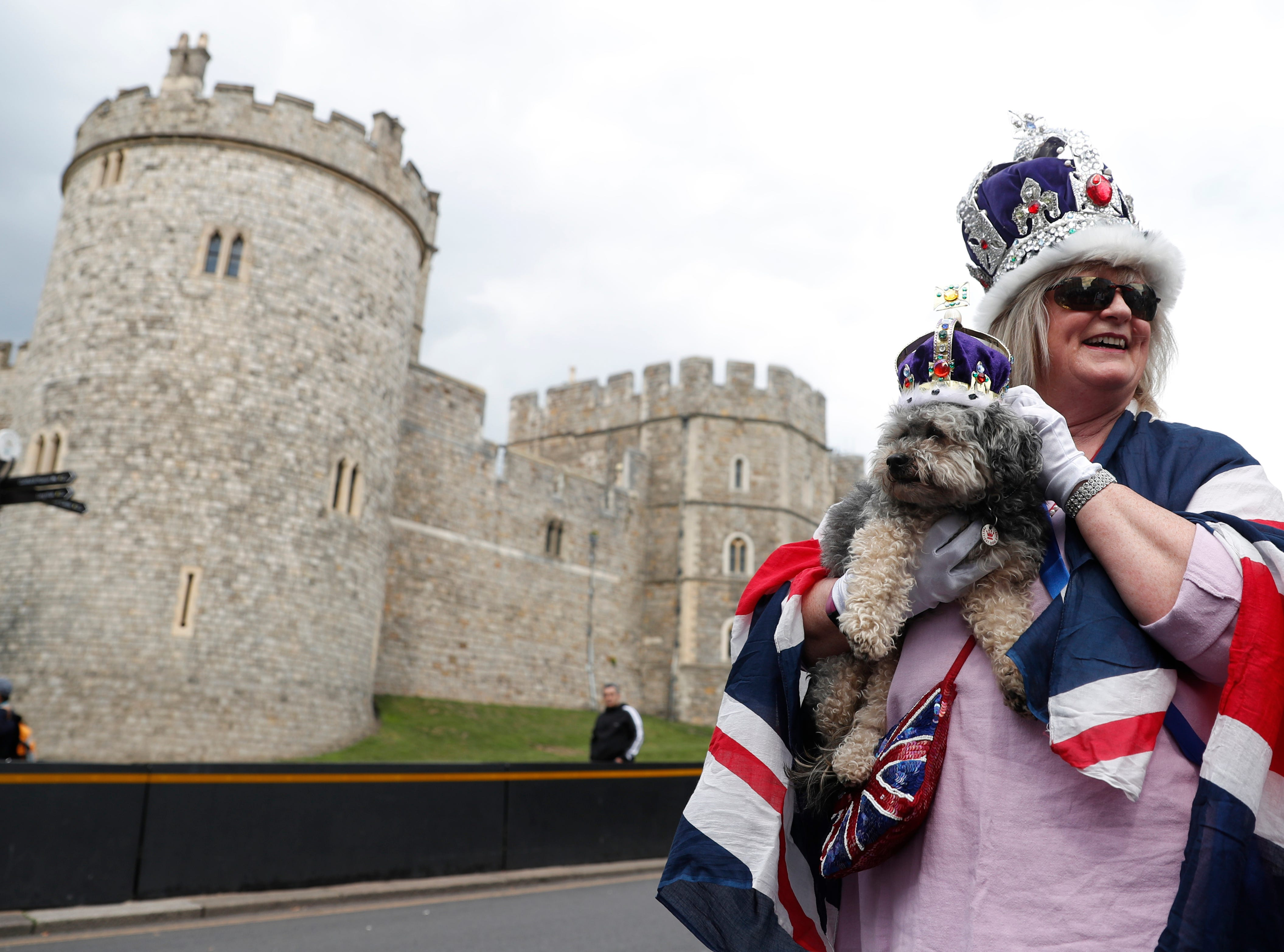 Royal fan Caroline Wagstaff and her dog Boots poses for the media outside Windsor Castle, Windsor, England, Tuesday May 7, 2019. The as-yet-unnamed baby arrived less than a year after Prince Harry wed Meghan Markle in a spectacular televised event on the grounds of Windsor Castle that was watched the world over.
