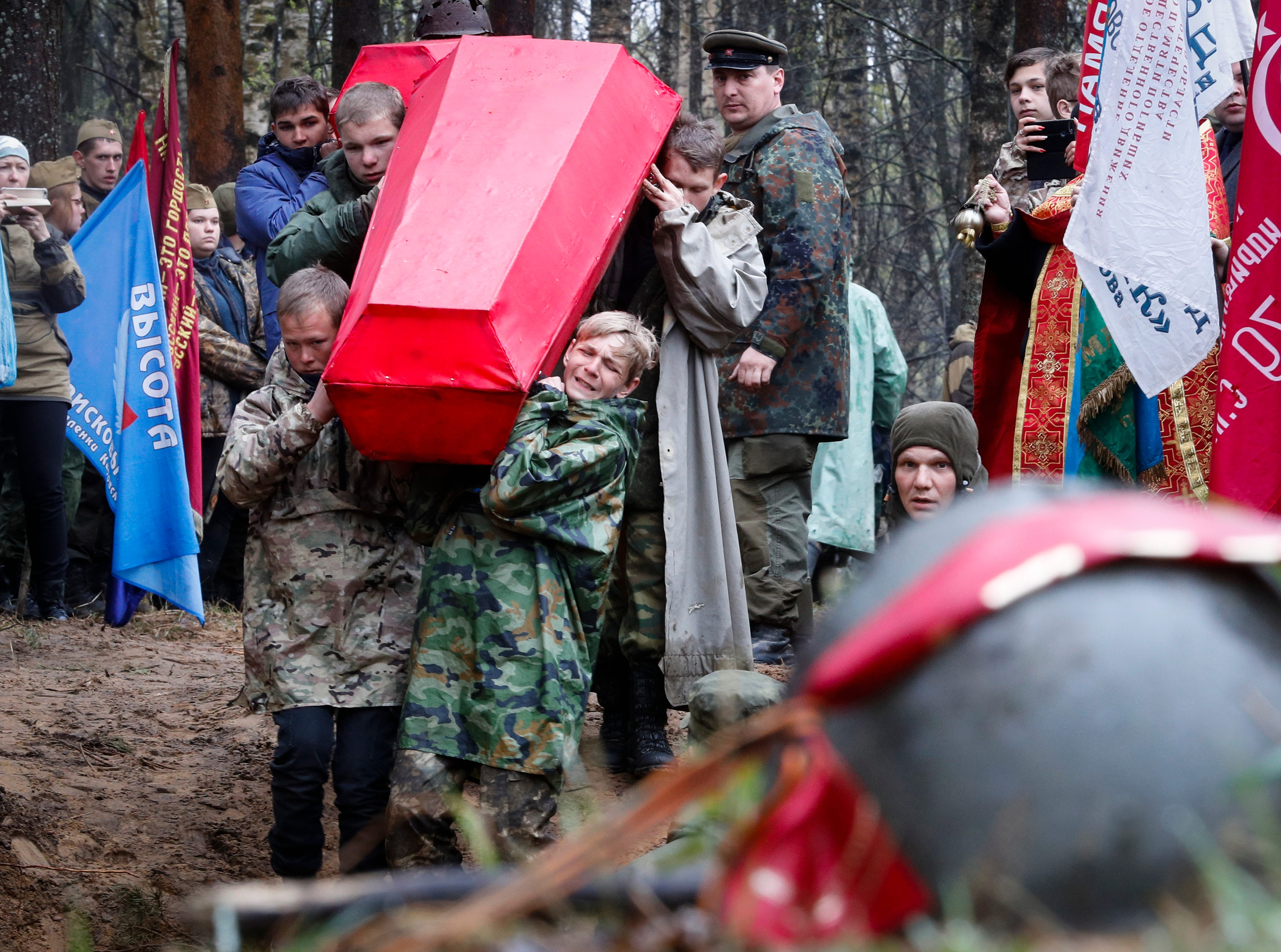 Members of volunteer search teams carry coffins with the remains of Soviet soldiers killed during World War II, during a reburial ceremony at the Sinyavino Heights memorial near the village of Sinyavino, 50 km (31 miles) east of St. Petersburg, Russia, Tuesday, May 7, 2019. Hundreds of people came to a World War II battleground outside St. Petersburg to bury the remains of 714 Soviet soldiers recovered by volunteer search teams. Forty one crimson coffins containing skulls and bones were solemnly buried at the Sinyavino Heights memorial as Russian war songs played and an honor guard fired a salute.