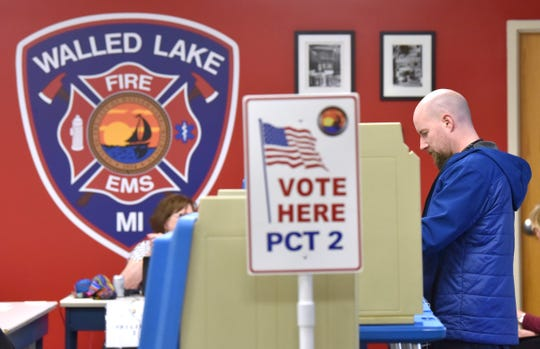 Bryan Stickradt of Walled Lake fills out his ballot at the Walled Lake Fire Department Headquarters on Tuesday.