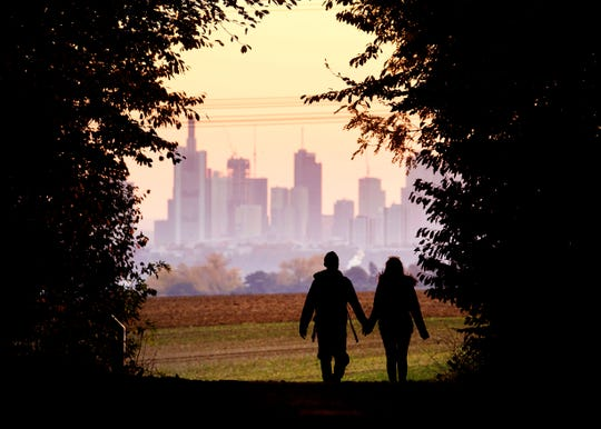 A couple walks through a forest with the  near Frankfurt, Germany.