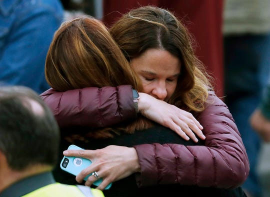 Parents hug as they wait for their children at the recreation center where students were reunited with their parents after a shooting at a suburban Denver middle school Tuesday, May 7, 2019, in Highlands Ranch, Colo.