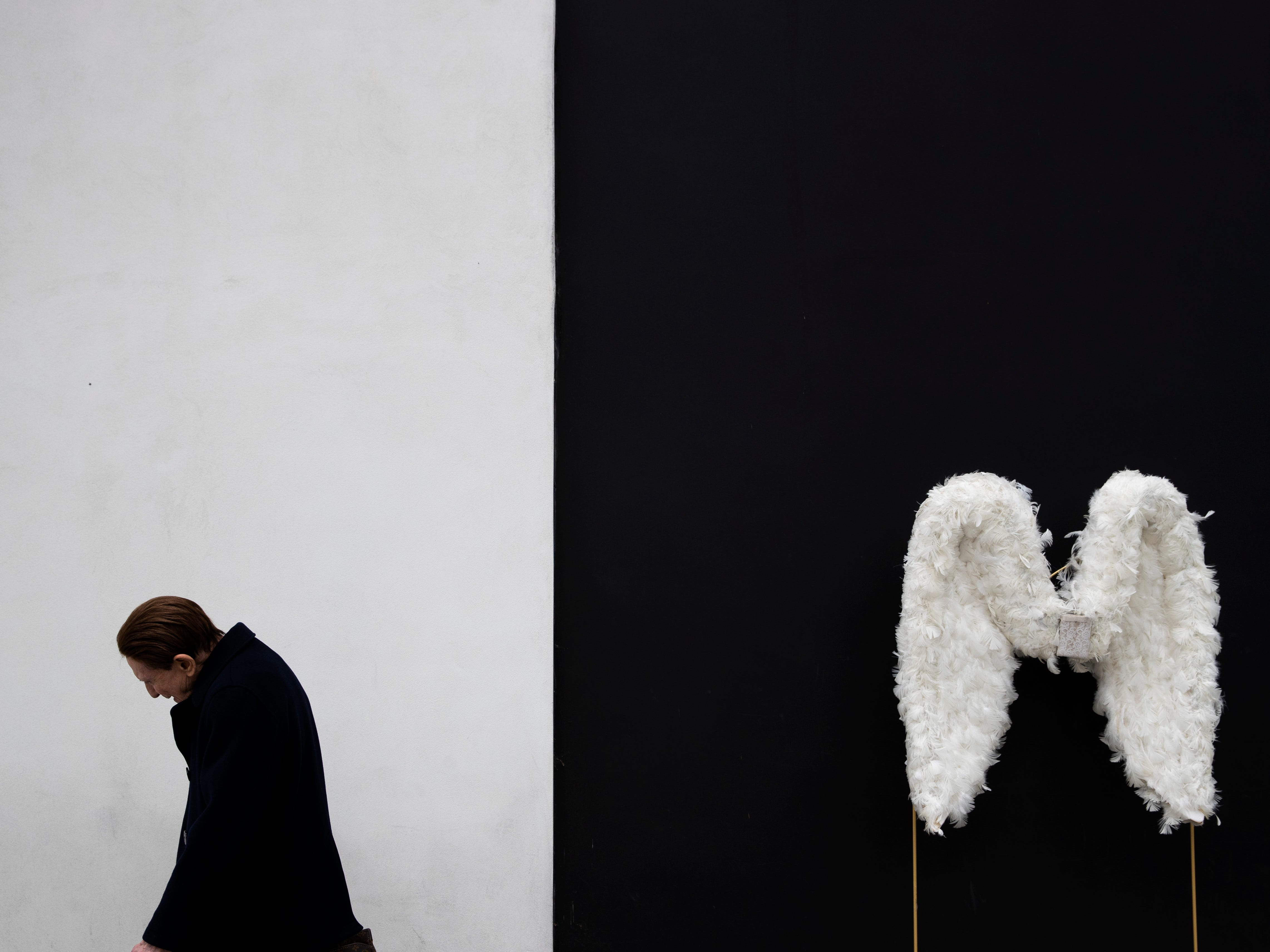 A man walks by a pair of angel wings as part of a store display in Beverly Hills, Calif., on Tuesday, May 7, 2019.