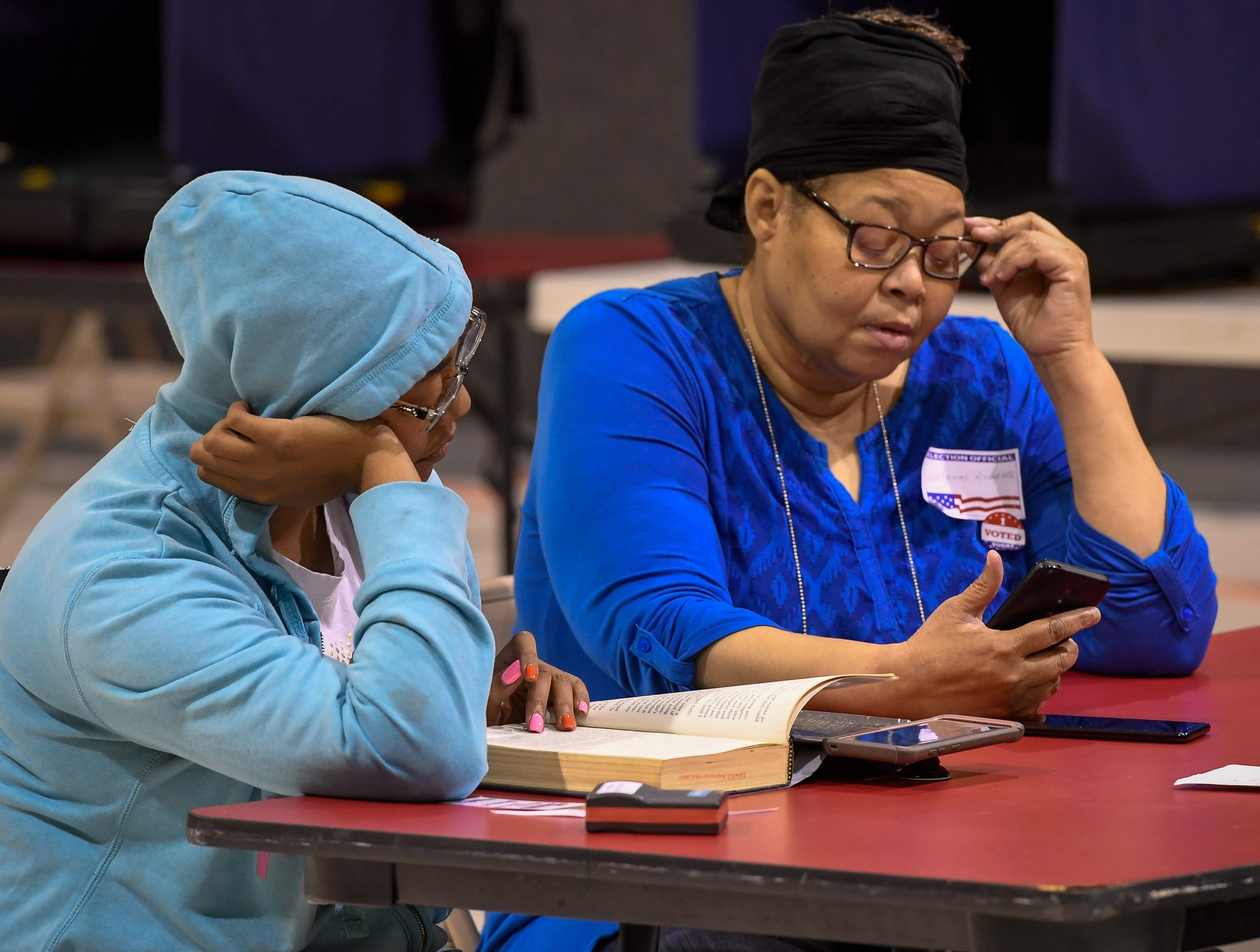 Election judges Tasha Ricketts, left, and her auntie Delores Ricketts pass the time waiting for voters at the Memorial Baptist Church voter center Tuesday, May 7, 2019.