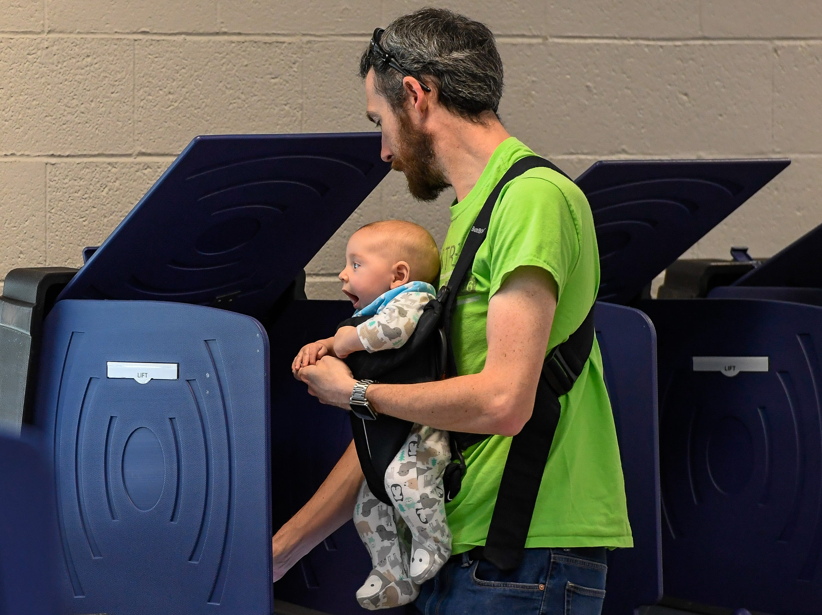 Emmett Williams casts his vote, with a little help from his son Gilbert Stevenson, three months-old, at the Methodist Temple on Lincoln Avenue in Evansville Tuesday, May 7, 2019.