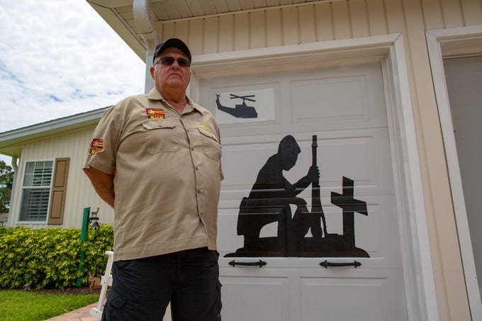 Bob Masson, 71 a Marine Vietnam War vet stands in front of his garage door that has a memorial mural at the Del Tura Golf & Country Club in North Fort Myers Tuesday, May 7, 2019. Community officialsÊsent Bob Masson, the mural's owner, a letter asking him to remove the depiction. Apparently there also had been a complaint.
