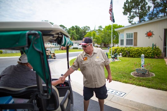 Bob Masson, 71 a Marine Vietnam War vet, right, shakes hands with his supporting neighbor who stopped to see the memorial mural at the Del Tura Golf & Country Club in North Fort Myers Tuesday, May 7, 2019. Community officialsÊsent Bob Masson, the mural's owner, a letter asking him to remove the depiction. Apparently there also had been a complaint.