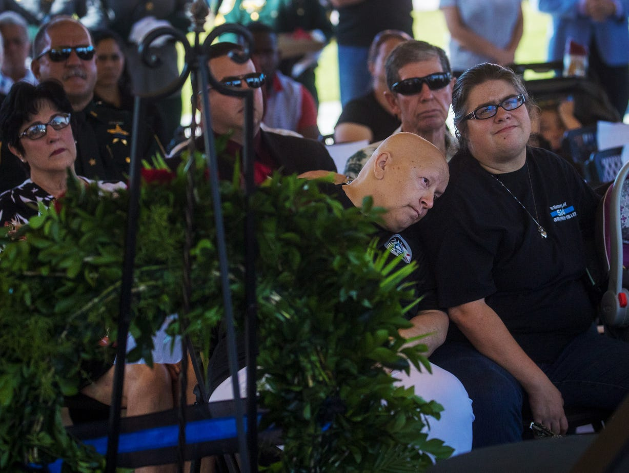 Patricia Miller, the mother of fallen Fort Myers Police officer, Adam Jobbers-Mllier rests her head on her daughter, Nicole Miller's shoulder as they attend the Lee County Fallen Officer Memorial Ceremony at Centennial Park on Tuesday May, 7, 2019.