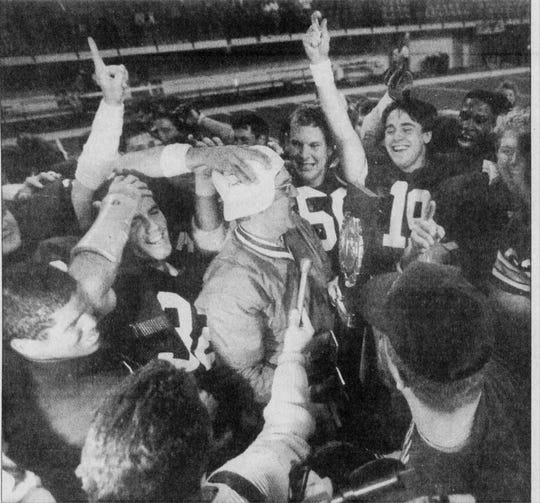 Jimmy Satterfield, with trophy in hand, is surrounded by jubilant Furman football players on Dec. 18, 1988